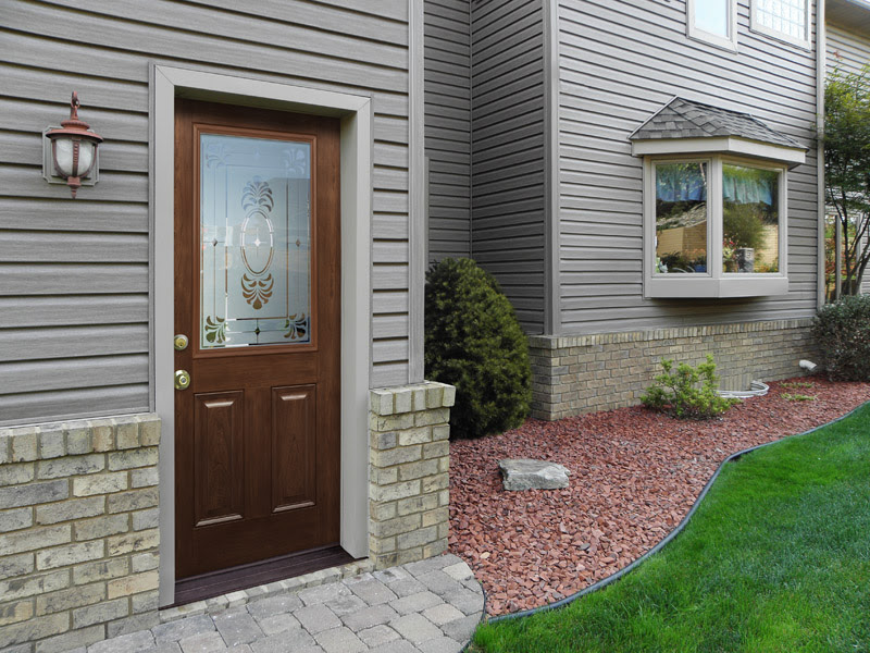 cherry wood entry door with a glass panel