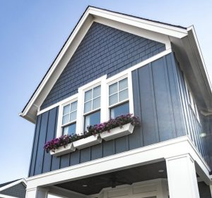 blue wide vertical siding on a home with white windows