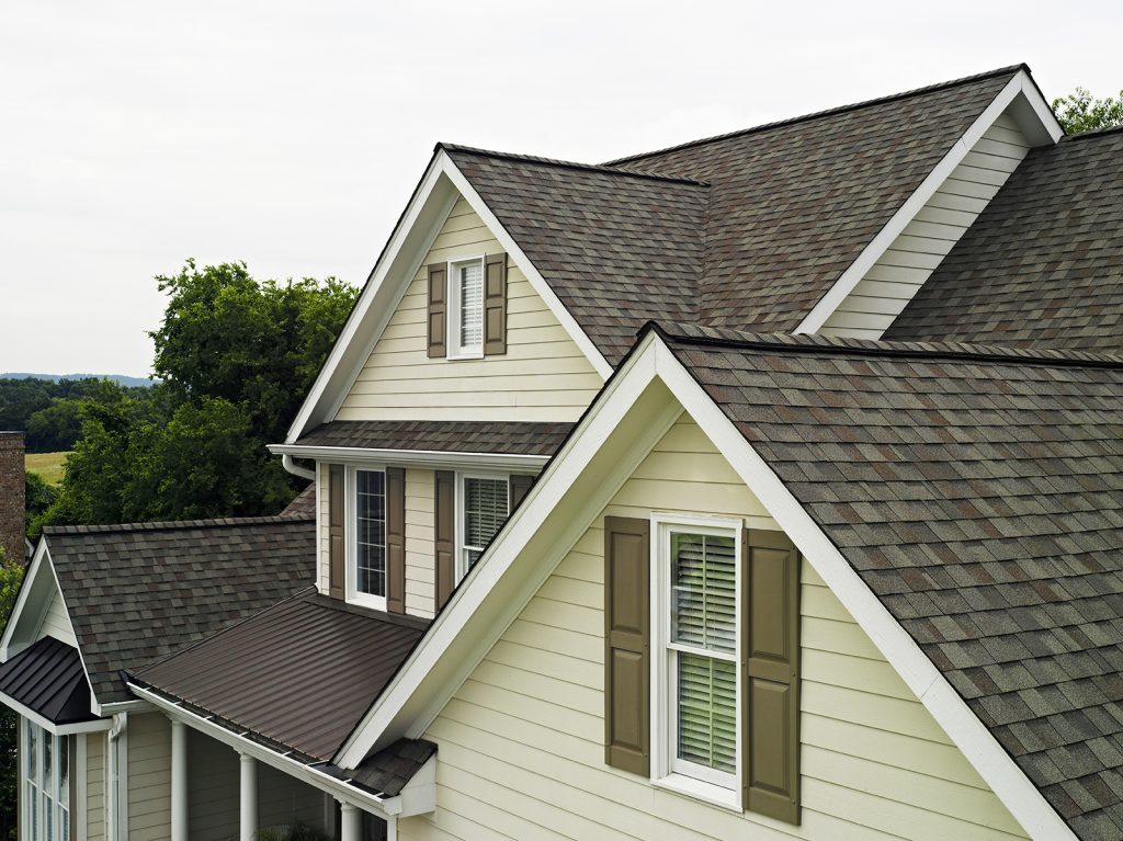 light gray and brown asphalt roof on home with yellow siding and brown shutters