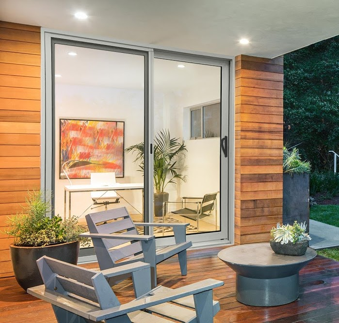modern patio sliding door that has a silver frame and leads to a patio
