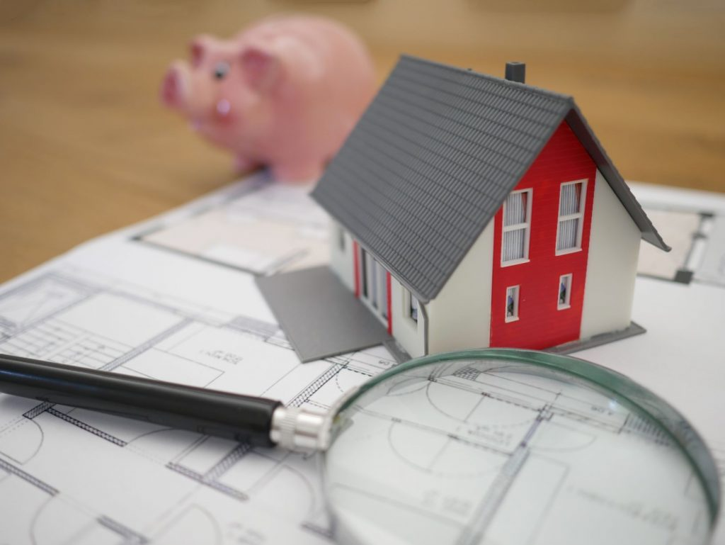 photo of model home sitting on blueprints with a piggy bank in the background