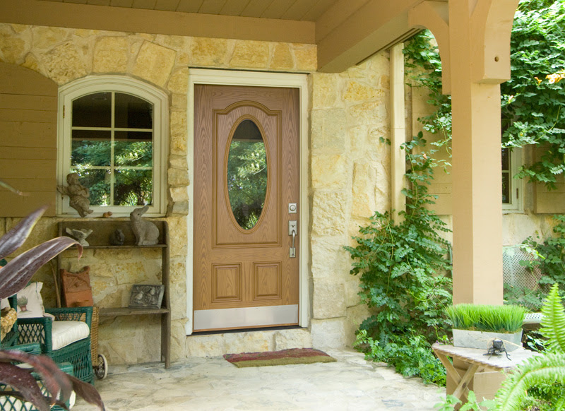 light brown entry door with an oval glass cut out
