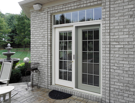white french doors opening on to a deck of a house with gray brick exterior